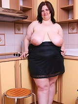 Teenage plumper demonstrates her curves in kitchen